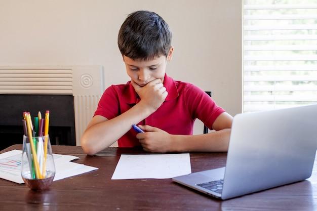 Formazione online a distanza. scolaro studia a casa e fa i compiti.