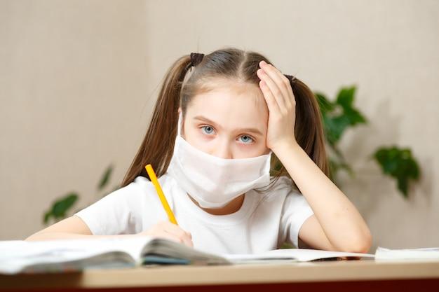 Formazione online a distanza. studentessa in maschera medica studiando a casa,
