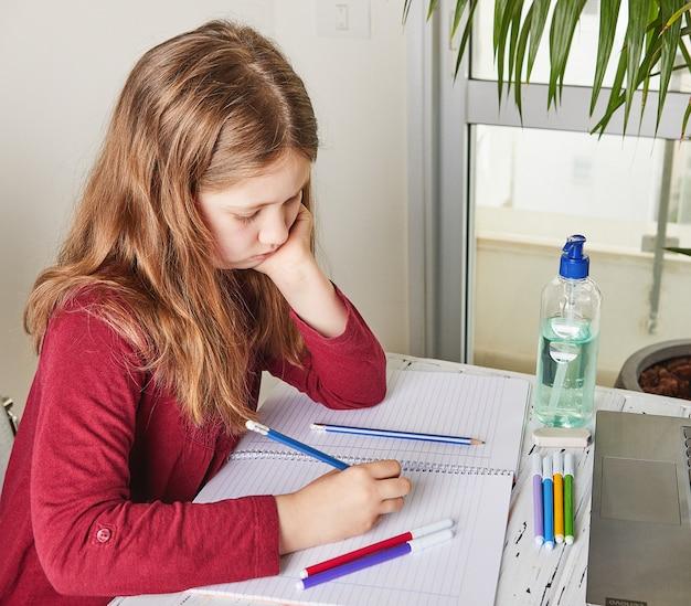 Formazione online a distanza. scolara che studia a casa con un computer portatile e che fa i compiti della scuola. libri di addestramento e pennarelli colorati sul tavolo, gel con alcool al 70 percento