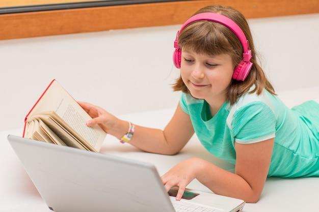 Formazione online a distanza. scolara che studia a casa con il taccuino del computer portatile e fa i compiti di scuola