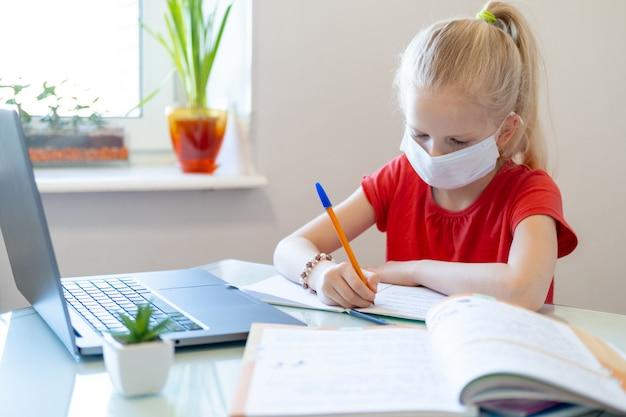 Formazione online a distanza. scolara di malattia nella maschera medica che studia a casa, esaminando il taccuino del computer portatile e facendo i compiti della scuola. libri di formazione e quaderni sul tavolo.