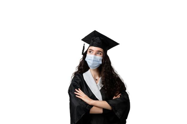 Apprendimento a distanza online con maschera medica nel periodo covid-19 del coronavirus. studia a casa. laurea dal college. laureato in abito nero sorridente. termina l'università e completa la laurea magistrale