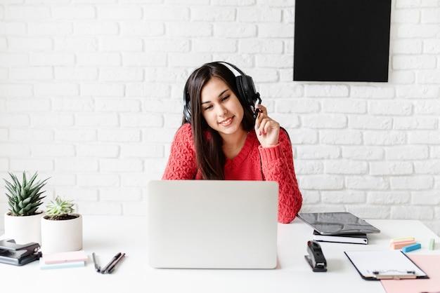 Apprendimento a distanza con la donna che insegna inglese online utilizzando il computer portatile