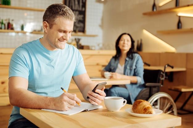 Lavoro a distanza. attraente gioioso uomo biondo ben costruito che tiene il suo telefono e scrive sul suo taccuino mentre una donna seduta su una sedia a rotelle in background