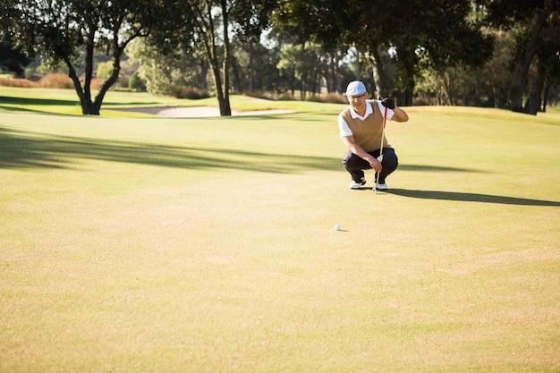 Vista in lontananza del golfista che si accovaccia e guarda la sua palla