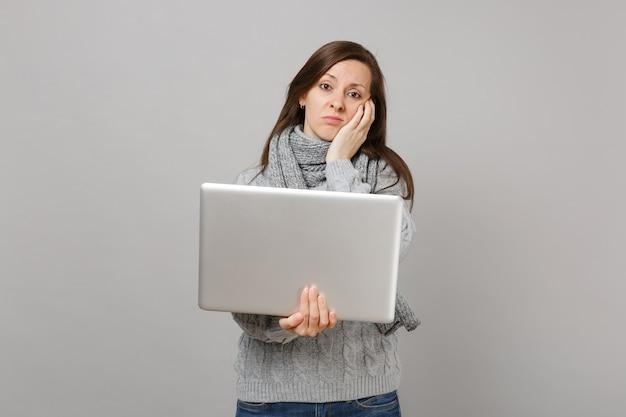 Giovane donna temperata in maglione grigio, sciarpa che mette mano sulla guancia lavorando su computer pc portatile isolato su sfondo grigio muro. consulenza per il trattamento online di uno stile di vita sano, concetto di stagione fredda.