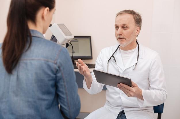 Distinto uomo intelligente e premuroso che si assicura che la signora gli parli di tutti i sintomi mentre cerca di capire la sua diagnosi