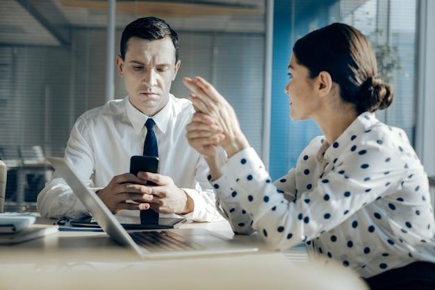 Distrae dall'argomento. bel giovane uomo seduto al tavolo accanto al suo collega di sesso femminile e controllando il suo telefono