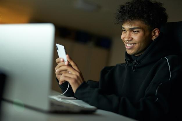 Ritratto di distrazione di uno studente maschio felice che sorride e utilizza lo smartphone mentre studia lavorando su