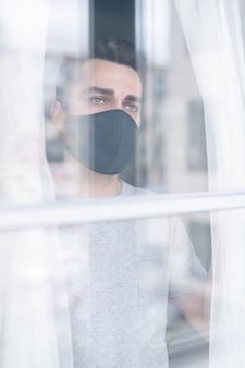 Giovane sconvolto in maschera protettiva in piedi alla finestra e sognando di uscire, concetto di quarantena