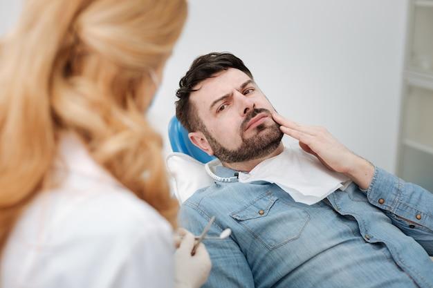 Disturbato bell'uomo sconvolto che racconta a un medico delle sue preoccupazioni mentre le paga una visita regolare e si siede sulla sedia del dentista