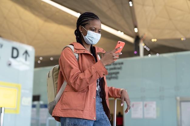 La donna disturbata in maschera protettiva legge il messaggio sullo smartphone aspetta la partenza dell'aereo in aeroporto