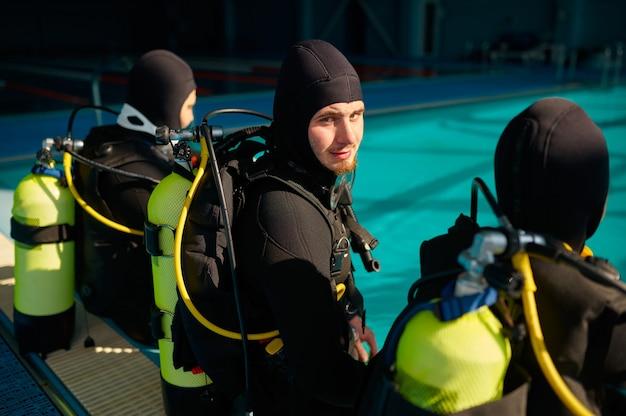 Divemaster e due subacquei in attrezzatura subacquea che si preparano per l'immersione, scuola di immersione. insegnare alle persone a nuotare sott'acqua, interno della piscina coperta sullo sfondo