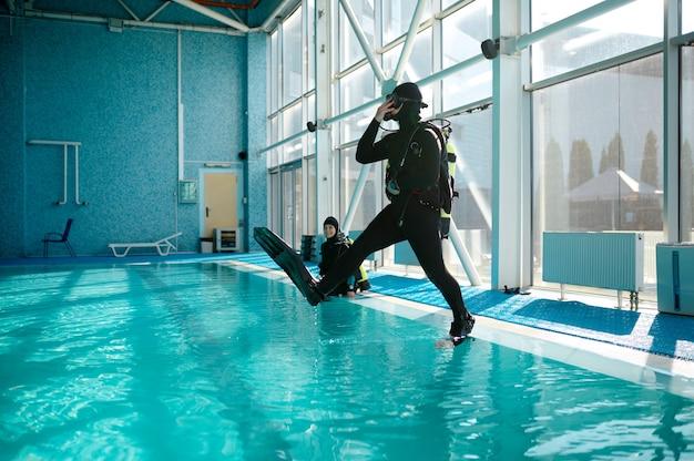 Il subacqueo in attrezzatura subacquea salta in piscina, lezione nella scuola di immersioni. insegnare alle persone a nuotare sott'acqua, nuoto al coperto. uomini con l'acqua lunga