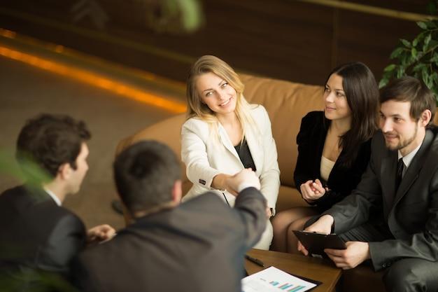 Una stretta di mano attraente diversificata del gruppo di affari della donna e dell'uomo all'edificio per uffici