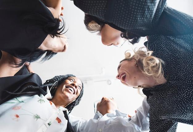 Diverse donne d'affari in una postura di abbraccio di gruppo
