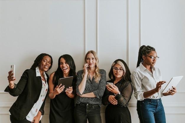 Diverse donne d'affari che utilizzano dispositivi digitali
