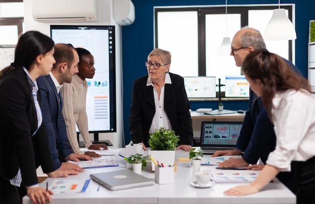 Diversi colleghi uomini d'affari che discutono di problemi aziendali durante la riunione di avvio seduti nell'ufficio di un'ampia sala. colleghi multietnici che lavorano pianificando una strategia finanziaria di successo discutendo in ufficio.