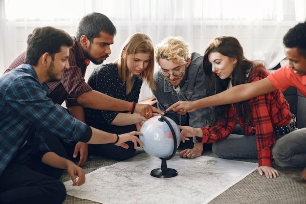 Diversi amici stanno andando per un viaggio. stanno pianificando di usare il globo. soggiorno luminoso.