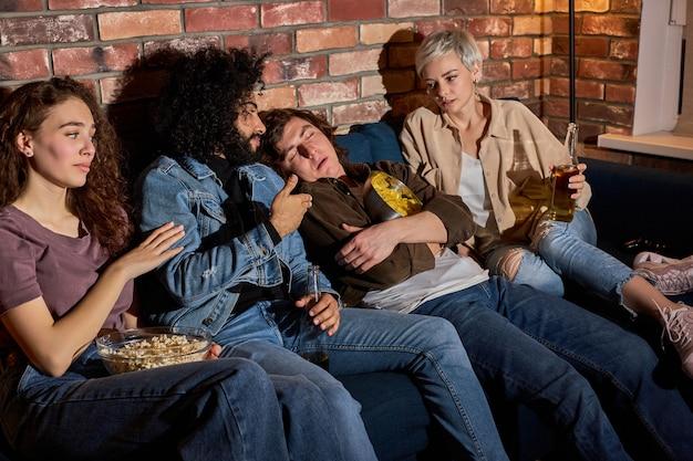 Diversi amici che guardano la tv mentre il ragazzo annoiato dorme nel soggiorno di casa, si addormenta durante il film, l'arredamento della casa