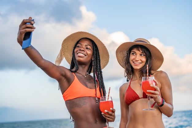 Diverse amiche che prendono selfie durante le vacanze estive sulla spiaggia