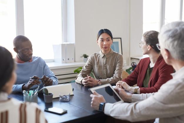 Diversi gruppi di uomini d'affari durante la riunione informativa in ufficio, si concentrano su una giovane donna d'affari asiatica che ascolta il capo