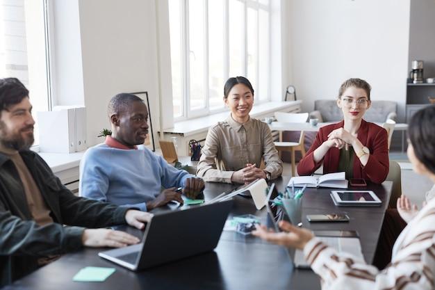 Diversi gruppi di uomini d'affari a tavola durante la riunione informativa in ufficio, si concentrano sulla donna asiatica sorridente che condivide idee