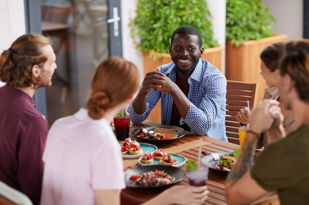 Gruppo eterogeneo di amici che godono insieme del pranzo