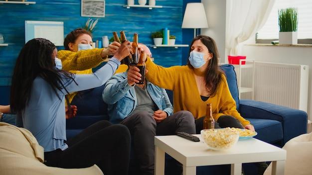 Diversi gruppi di amici che guardano la tv insieme sitcom comica mangiando snack e bevendo birra, facendo tintinnare bottiglie e divertendosi alla nuova festa normale, indossando una maschera protettiva contro il virus covid 19