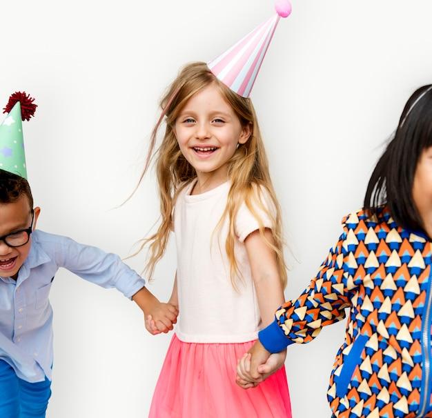 Diverso gruppo di bambini che si tengono per mano in cappello festivo