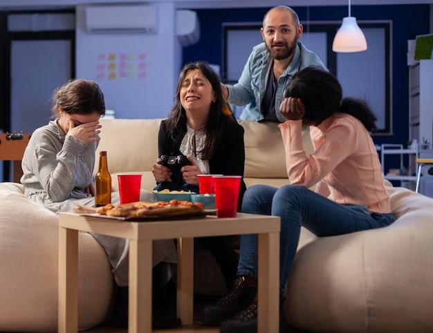 Diversi gruppi di compagni che si legano durante la riproduzione di videogiochi sulla console tv perdendo con il controller joystick dopo il lavoro. il team multietnico si gode la festa in ufficio con snack e bevande