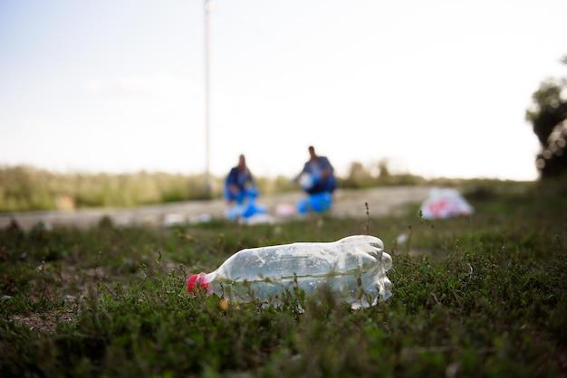 Gruppo eterogeneo di persone che raccolgono rifiuti nel servizio comunitario di volontariato del parco.