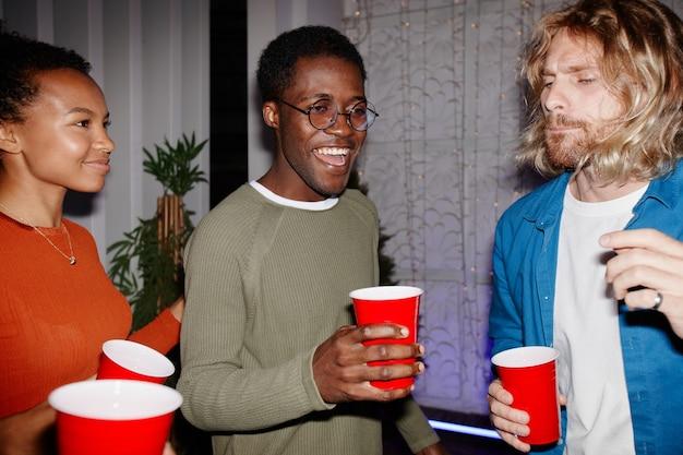 Gruppo eterogeneo di giovani che si godono la festa in casa al chiuso e tengono in mano tazze rosse, sparate con il flash