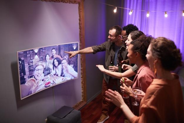 Diversi gruppi di giovani che parlano con gli amici online mentre si godono la festa a casa