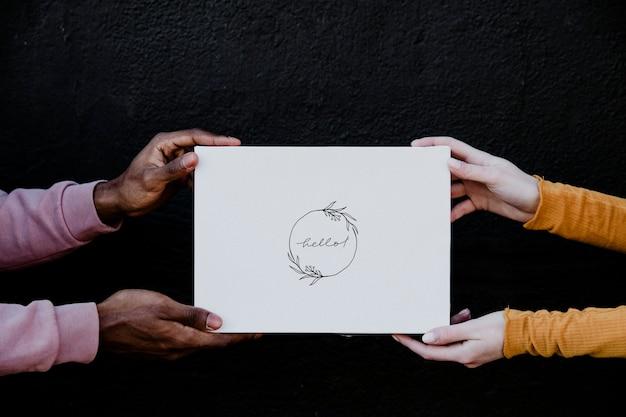 Diverse mani che tengono una carta mockup con il testo