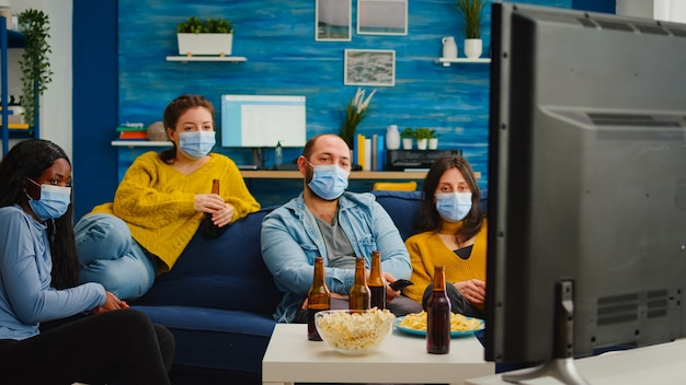 Diverse persone che si rilassano insieme guardando la tv tenendo il telecomando mantenendo le distanze sociali indossando la maschera durante l'epidemia di coronavirus per prevenire le malattie. godendo la festa bevendo birra e mangiando patatine?