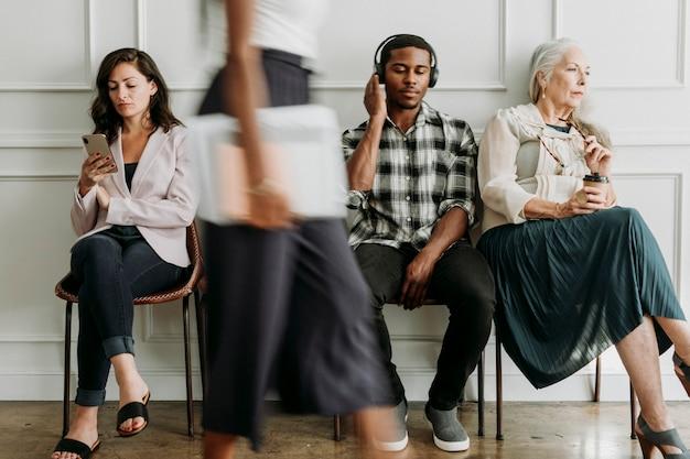 Diverse persone sedute vicino a un muro bianco