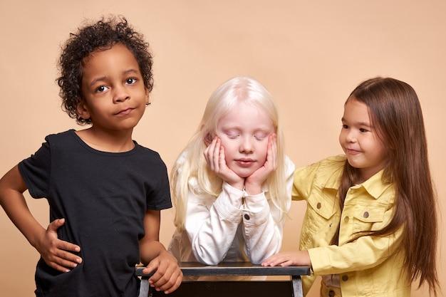 Diversi bambini positivi sorridenti che propongono felici insieme