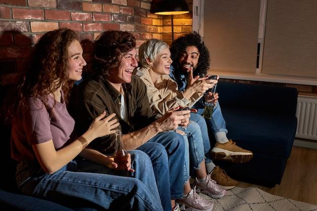 Diversi studenti che si divertono a giocare ai videogiochi, riposano a casa. sorridendo, gli americani eccitati si divertono con i joystick nell'interno del soggiorno, nello spazio libero,