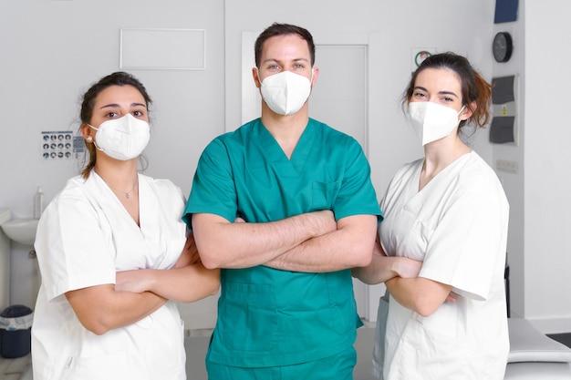 Un team eterogeneo di professionisti sanitari che indossa una maschera protettiva che lavora in una clinica di riabilitazione fisica durante la pandemia di coronavirus