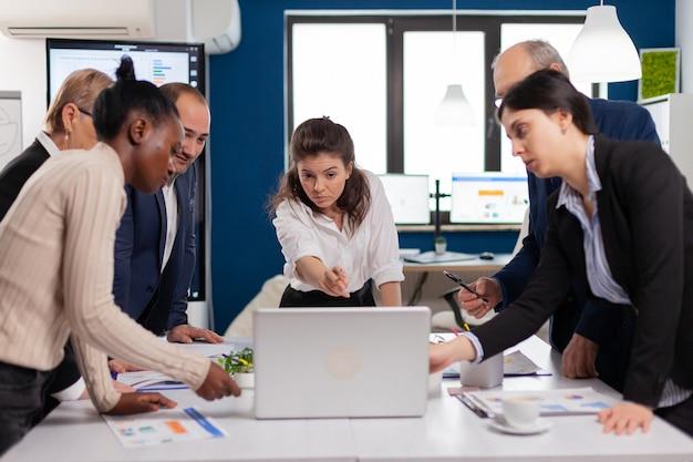 Diversi team di lavoratori che parlano, guardano documenti e analizzano i dati dei grafici in piedi alla scrivania della conferenza. colleghi multietnici che lavorano pianificando una strategia finanziaria di successo che discutono in ufficio
