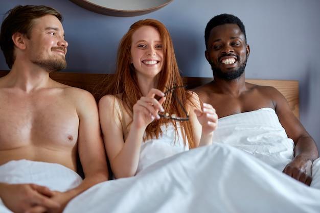 Trio diversificato che fa l'amore in camera da letto