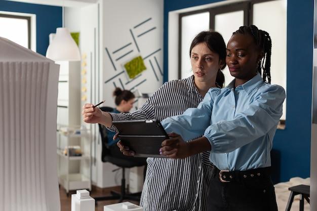 Diversi team di lavoro di architetti multietnici che lavorano su tablet che controllano il piano di costruzione di m...