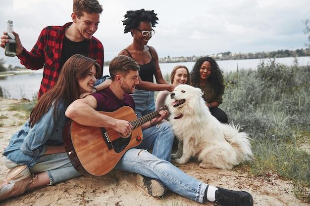 Diversità delle persone. fare picnic sulla spiaggia. gli amici si divertono durante il fine settimana.