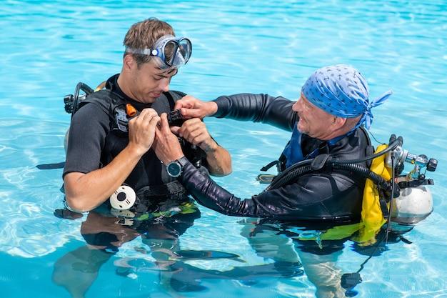 L'istruttore subacqueo aiuta il suo studente a proteggere l'attrezzatura subacquea