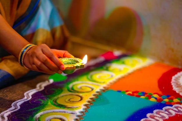 Diwali o festa delle luci. festival indiano tradizionale di diwali, mani di donna che tengono lampada a olio