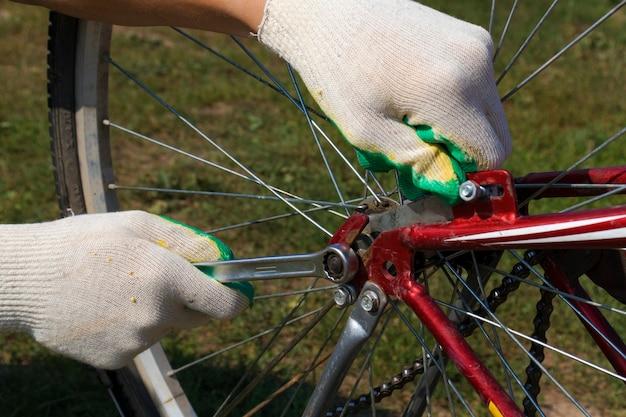 Riparazione bici fai da te. l'immagine del primo piano della mano del ciclista ripara la ruota della bicicletta.