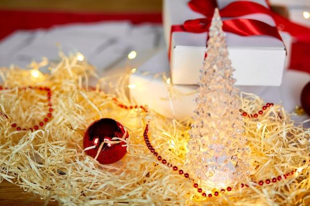 Confezione regalo di natale fai da te scatola bianca regalo di natale con un nastro rosso, decorazione festiva sul tavolo.