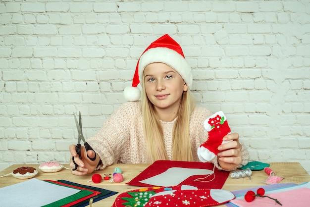 Calza natalizia fai da te, ragazza con calzino natalizio in feltro fatto a mano