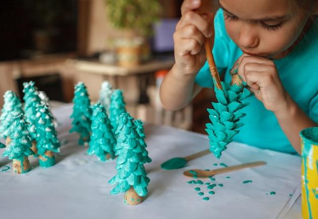 Regali artigianali fai da te e decorazioni natalizie. ragazza che colora il cono come se fosse un pino, sii verde